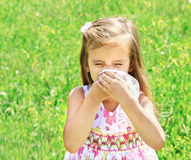 Little girl is blowing her nose on green meadow. Allergy Royalty Free Stock Photos