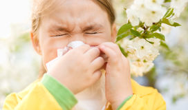 Little girl is blowing her nose. Near spring tree in bloom Royalty Free Stock Photos