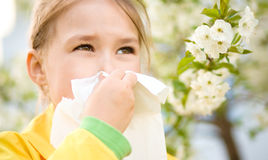 Little girl is blowing her nose. Near spring tree in bloom Stock Image