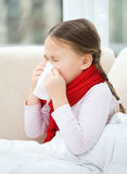 Little girl is blowing her nose. While sitting on a sofa Stock Photography