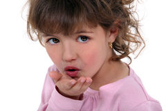 Little girl blowing kiss. At the camera Royalty Free Stock Photo