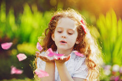 Little girl blowing rose petals from her hand. S Royalty Free Stock Photo