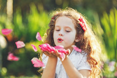 Little girl blowing rose petals. From her hands. Fresh, healthy respiration concept Royalty Free Stock Photos