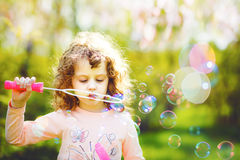 Little girl blowing soap bubble. Stock Photos