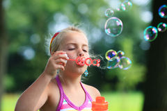 Little girl blowing soap bubble outdoor Royalty Free Stock Photo