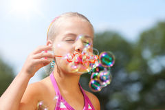 Little girl blowing soap bubble outdoor Stock Photography