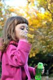 Little girl blowing soap bubbles Stock Images