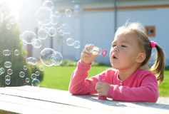 Little girl is blowing soap bubbles Royalty Free Stock Photos