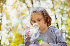 Little girl blowing soap bubbles. Outdoors with beautiful bokeh background Stock Photos
