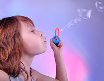 Little girl blowing soap bubbles in bright surrounding. Little girl blowing soap bubbles in bright pink and blue surrounding Royalty Free Stock Photography