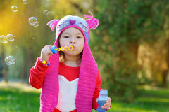 Little girl blowing soap bubbles, closeup portrait Stock Image