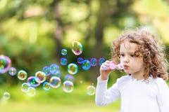A little girl blowing soap bubbles, closeup portrait beautiful c