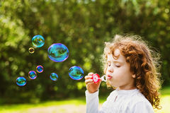A little girl blowing soap bubbles, closeup portrait beautiful c Royalty Free Stock Photos