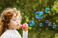 A little girl blowing soap bubbles, closeup portrait beautiful c Royalty Free Stock Image