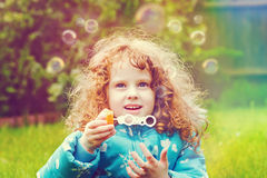 Little girl blowing soap bubbles, closeup portrait beautiful cur Royalty Free Stock Images
