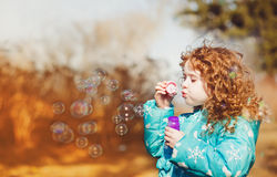 A little girl blowing soap bubbles Royalty Free Stock Image