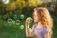 Little girl blowing soap bubbles. Little curly girl blowing soap bubbles stock image