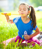 Little girl is blowing a soap bubbles Stock Photography