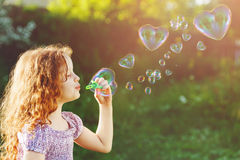 Little girl blowing soap bubbles, happy childhood concept. Royalty Free Stock Images