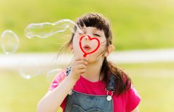 Little girl blowing soap bubbles outdoors Stock Images