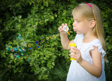 Little girl blowing soap bubbles. Royalty Free Stock Photos