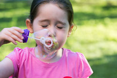 A little girl blowing soap bubbles in a park Royalty Free Stock Image