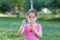 A little girl blowing soap bubbles in a park Stock Image