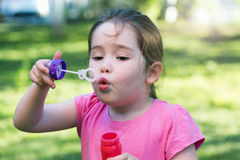A little girl blowing soap bubbles in a park Stock Photography