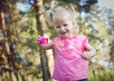 Little girl blowing soap bubbles. Little girl in a red dress,  blowing soap bubbles Royalty Free Stock Photo