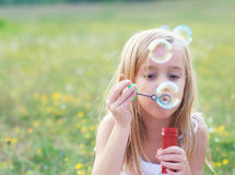 Little girl blowing soap bubbles on spring meadow Stock Photo