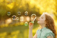 Little girl blowing soap bubbles in spring outdoors royalty free stock photo