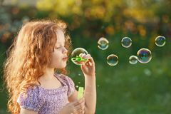 Little girl blowing soap bubbles in spring outdoors royalty free stock images