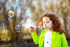 A little girl blowing soap bubbles, spring portrait beautiful cu Royalty Free Stock Images