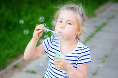 A little girl blowing soap bubbles. At summer Stock Photos