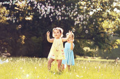 Little girl blowing soap bubbles on a summer meadow Royalty Free Stock Image