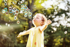 Little girl blowing soap bubbles on a summer meadow Stock Photo