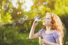 Little girl blowing soap bubbles in summer park. Background toninf for instagram filter Stock Photos