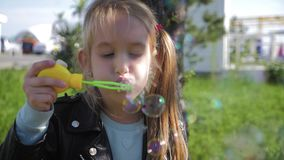Little girl blowing soap bubbles in summer park. Slow mo video. stock video footage