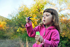 Little girl blowing soap bubbles to windward Stock Images