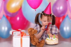Little girl blowing in tubule. Little girl in the cap blowing in tubule on her Birthday Royalty Free Stock Images