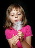 Little girl blowing into white feather Royalty Free Stock Image