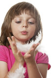 Little girl blowing on white feather Royalty Free Stock Photography