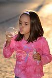 Little girl blows a bubble Stock Image
