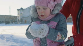 A little girl blows hands the snow with his mother stock video footage