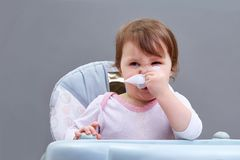 The little girl blows her nose into a paper handkerchief on grey background. The little girl blows her nose into a paper handkerchief sitting in feeding chair on Royalty Free Stock Image