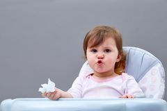 The little girl blows her nose into a paper handkerchief on grey background. The little girl blows her nose into a paper handkerchief sitting in feeding chair on Royalty Free Stock Photography