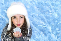 Little girl blows magic snowflake on winter background. Pretty little girl blows magic snowflake on frozen winter background Stock Photo