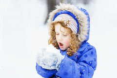 Little girl blows snow with mittens, on a snowflakes bokeh backg Royalty Free Stock Images