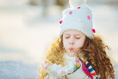 Little girl blows snow with mittens, on a snowflakes bokeh backg Stock Image