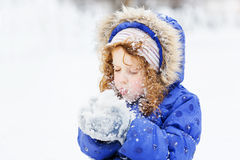 Little girl blows snow with mittens, on a snowflakes bokeh Royalty Free Stock Photography